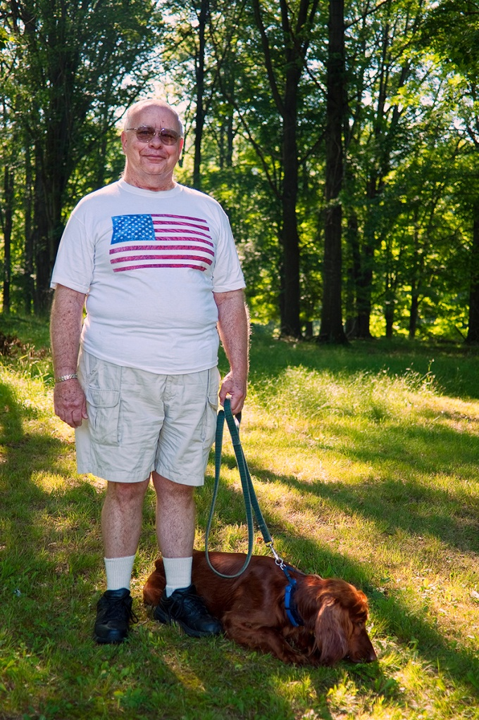 Image of man in American flag tee-shirt walking his Irish setter on the 4th of july