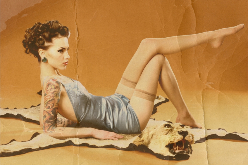This is a distressed image of a pin up girl wearing blue lingerie lounging on a lion skin rug on a orange background.