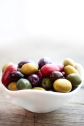 This is an image of a variety of different colored olives in a small white bowl, white window background.